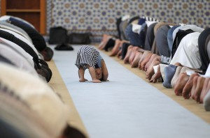 A child is seen near members of the Muslim community attending midday prayers at Strasbourg Grand Mosque in Strasbourg